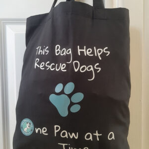 A black tote bag with One Paw at a Time branding