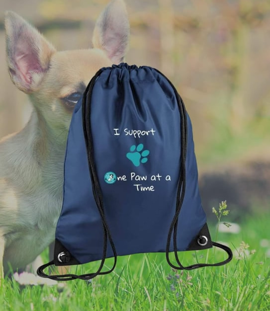 A black drawstring bag showing the text 'I support One Paw at a Time'